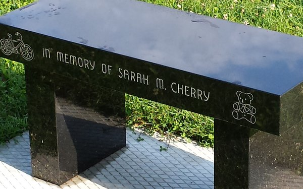 Closeup of dedication inscription of memorial bench at the Memorial for Maine Murdered Children in Augusta, ME.