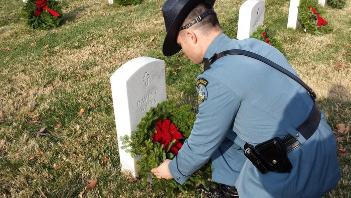 Maine State Trooper Steve Morrill lays a wreath on the grave of David Wales.