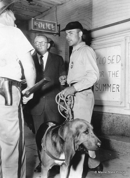 "1964-NH Trooper handler Eugene Meier and ""Chief"" the hound that found alleged murderer Joseph McDonald. On left, Public Safety Commissioner Robert Rhodes. Photo taken in Somersworth NH."