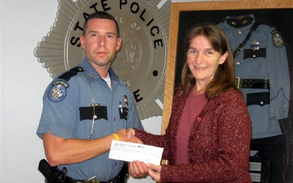 Aaron Turcotte, Treasurer of the Maine State Troopers Foundation, presents a check to Vicki Dill of the Maine Chapter of Murdered Children.